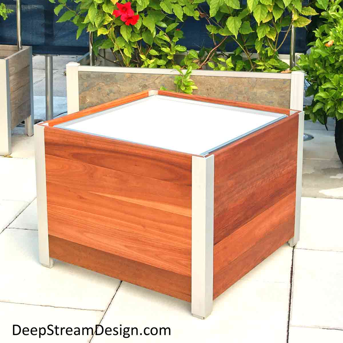 A Modern Planter handmade from Cumaru wood to custom specifications by American craftsmen, shown unplanted with a waterproof planter liner inside that is supported by a hidden structural aluminum frame. Behind the Modern  Wood Planter is a larger Modern Planter handcrafted from natural slate with a trellis frame covered in a green vine with bright red flowers that acts as a privacy screen blocking the view of air conditioning equipment behind it on a tropical roof deck.