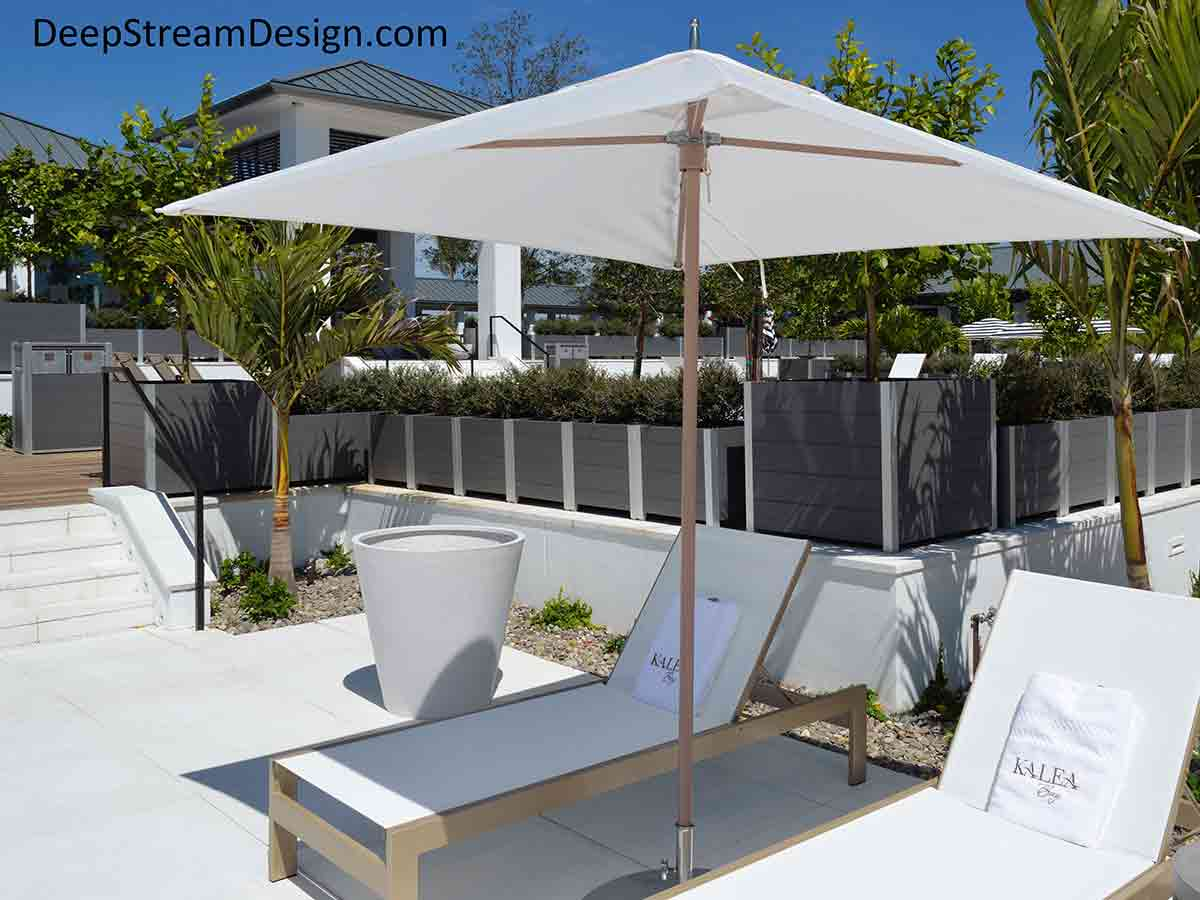 A long row of sleek gray Modern Planters, both rectangular and square large planters for trees create a safety wall between levels at a chic luxury condo development pool and club house with white sunbeds and white monogramed towels under bright white umbrellas.