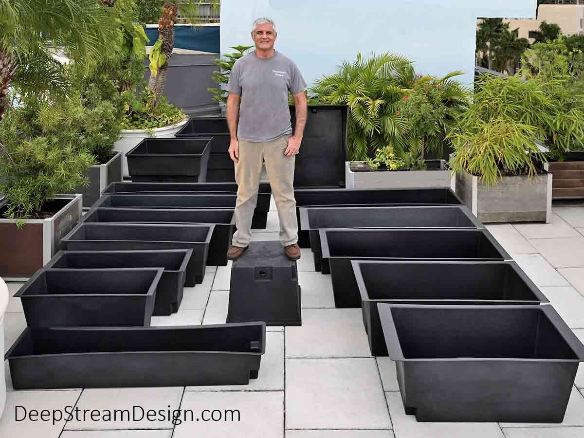 On a green tropical jungle landscaped roof terrace, a large man is standing on the top of one of sixteen stock rotomolded 100% recycled LLDPE food safe UV-stabilized plastic planter liners with advanced drainage to show how strong they are.