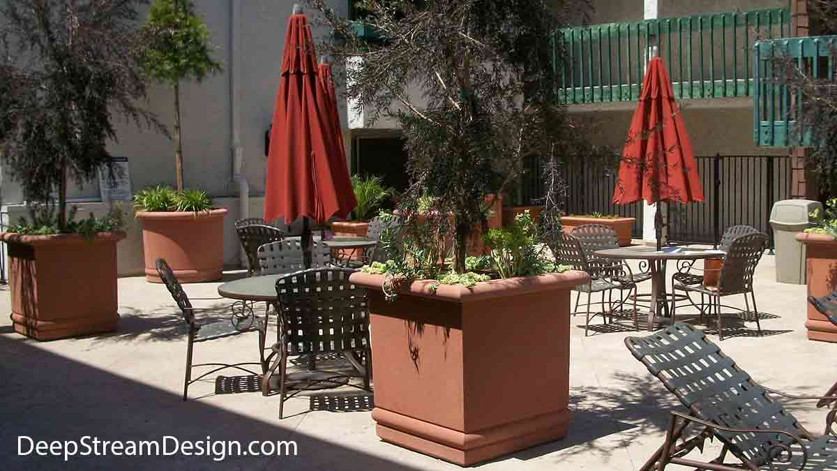 In a rustic terracotta color, the Florence Collection, exhibited here on a hotel pool desk with red umbrellas and iron furniture, recalls the Renaissance revival in high quality Concrete Planters and Pots with rounded scroll-top. The round accents in the lower portion are an elegant addition to the design imparting a Mediterranean influence on these very large round and cube shaped Concrete Garden Planters seen here planted with trees.