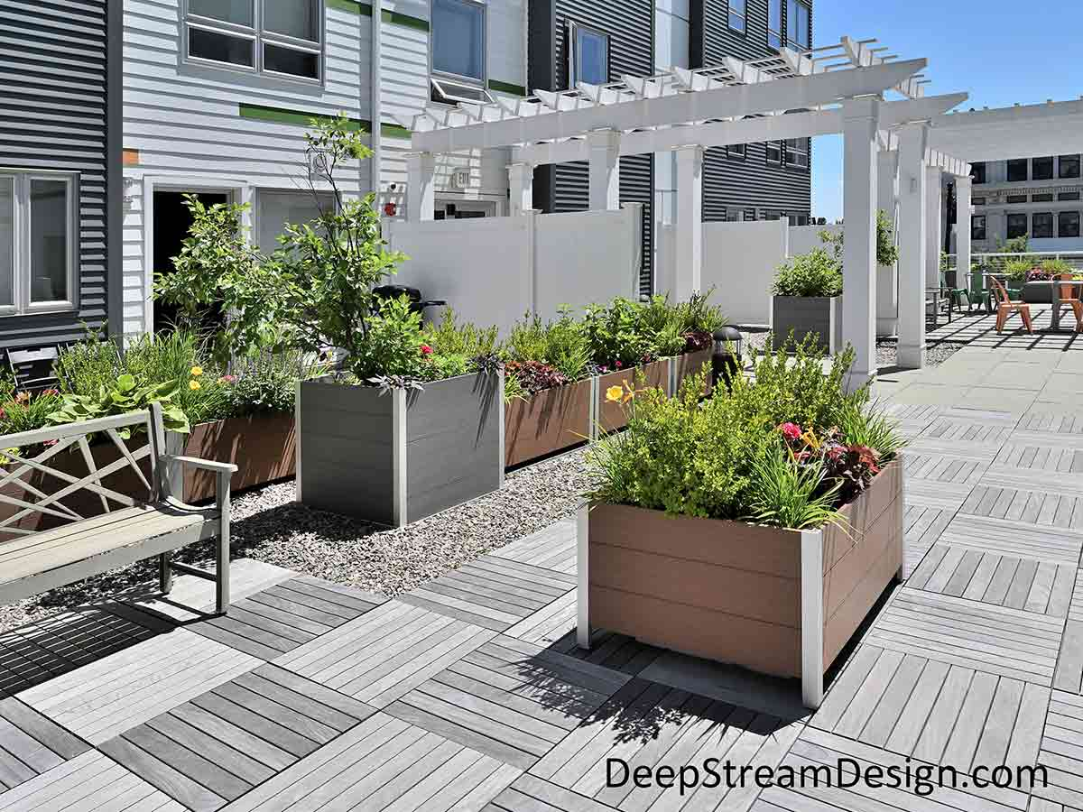 Many square and rectangular Large Wood Garden Planters crafted from maintenance free recycled plastic lumber landscape the central common area terrace of an apartment building with bushes, trees, and flowers.
