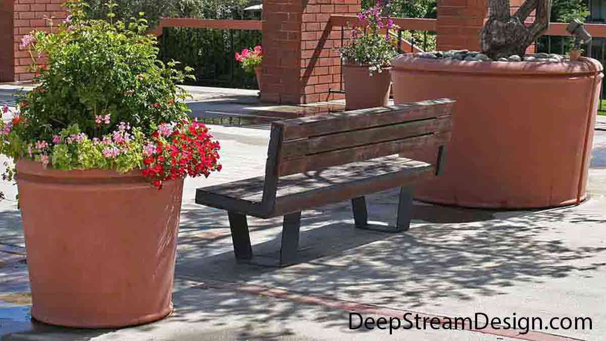 A plaza bench sits under a tree growing in the largest of 3 sizes of round, slightly tapered, very large high quality Concrete Planters. The Village series of Concrete Garden Planters is decorated only with an indented reveal just under the rim.