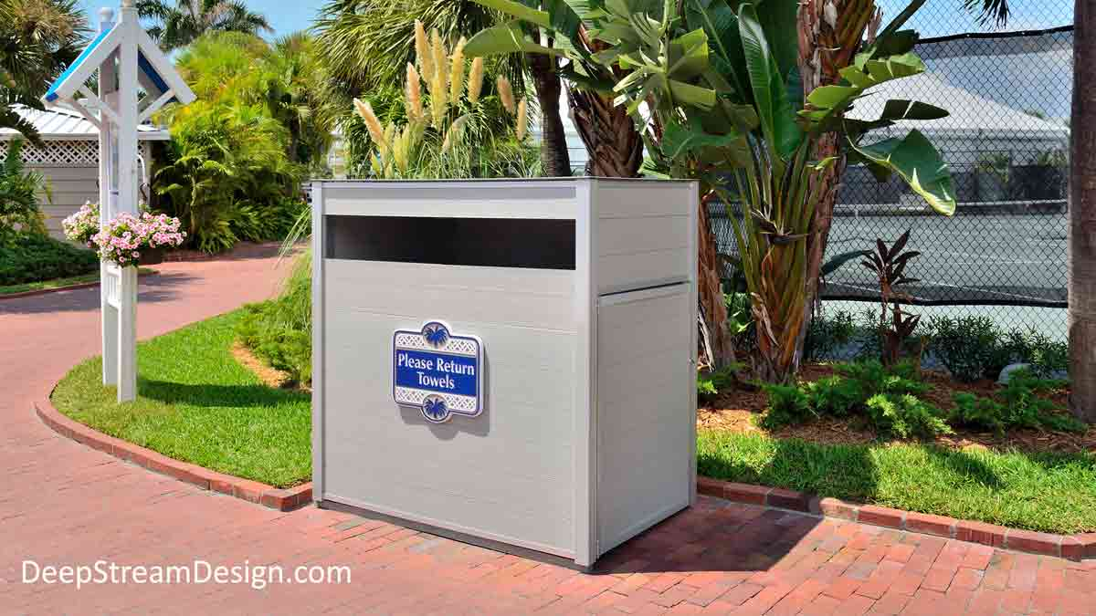 A Weatherproof Pool Towel Return Cart Cabinet in a lushly landscaped resort between the pool, beach, and tennis courts surrounded by palm trees and banana plants.
