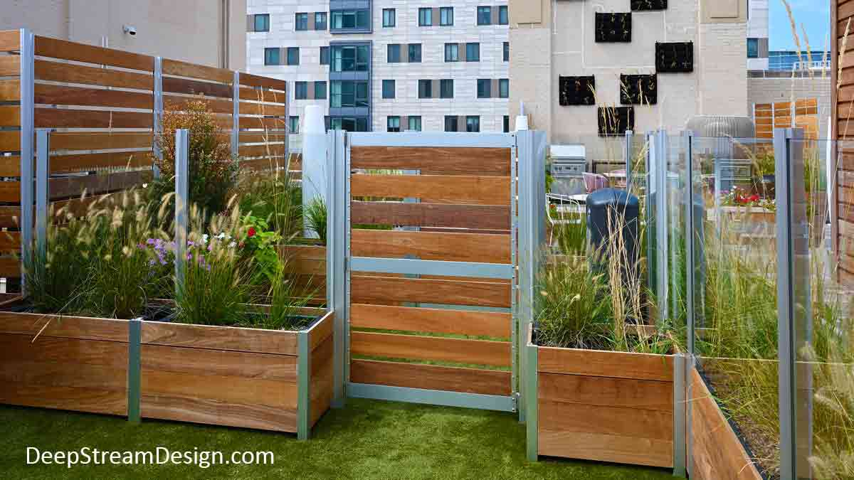 Large wood Planters with Gates are part of a wood and glass screen wall enclosure anchored by wood garden planters that form an expansive dog park on the roof terrace of an urban apartment building.