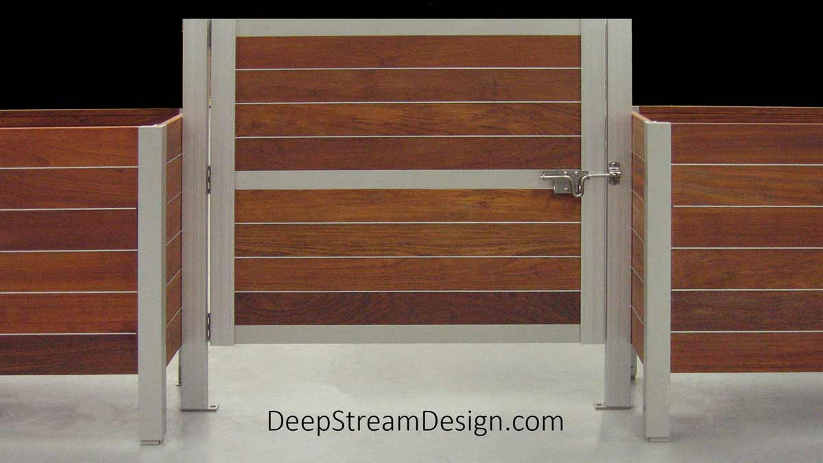 A detailed studio photo showing two wood Planters with a Gate that is taller than the wood planter boxes held by DeepStream's custom anodized aluminum gate's horizontal and vertical frame. The gate is mounted with two custom 316 stainless steel hinges and held closed by a simple 316 stainless steel slide bolt latch.
