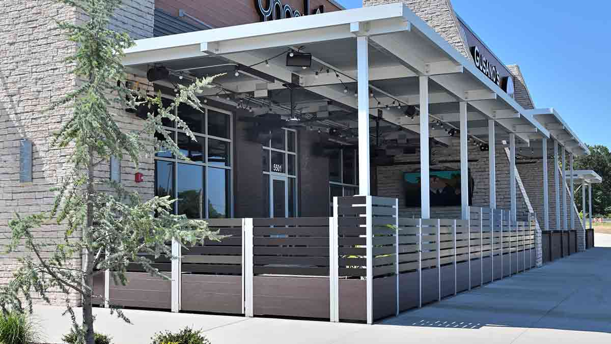 Exterior view of Planter mounted bronze anodized aluminum Screen Wall and Planters with Gates controls access to a restaurant's exterior smoking area, while meeting life safety codes.