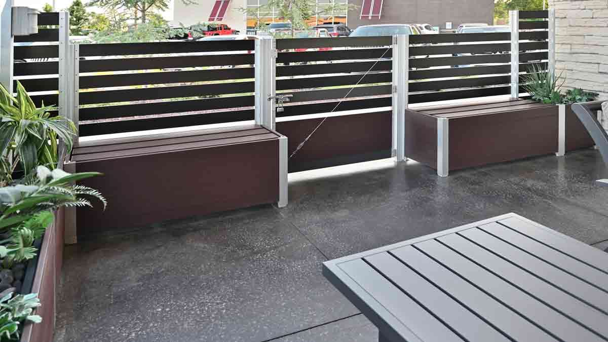 Detailed interior view of DeepStream Designs' benches and modular Mariner Long Wood Garden Planters with Gates that meet life safety codes for exits, an important part of the screen wall enclosing an upscale restaurant's outdoor smoking area.