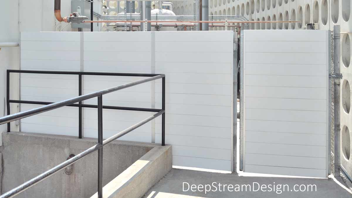 Planters with Gates and white HDPE screen wall are incorporated in the backside of a security enclosure, preventing access to dangerous equipment.