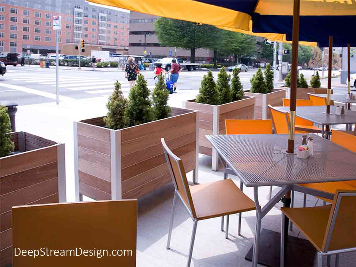 These DeepStream's natural wood planters, shown creating an urban sidewalk café under bright umbrellas, have an internal structural aluminum frame that holds separate planter liners, making them easy to retrofit with gates at any time.