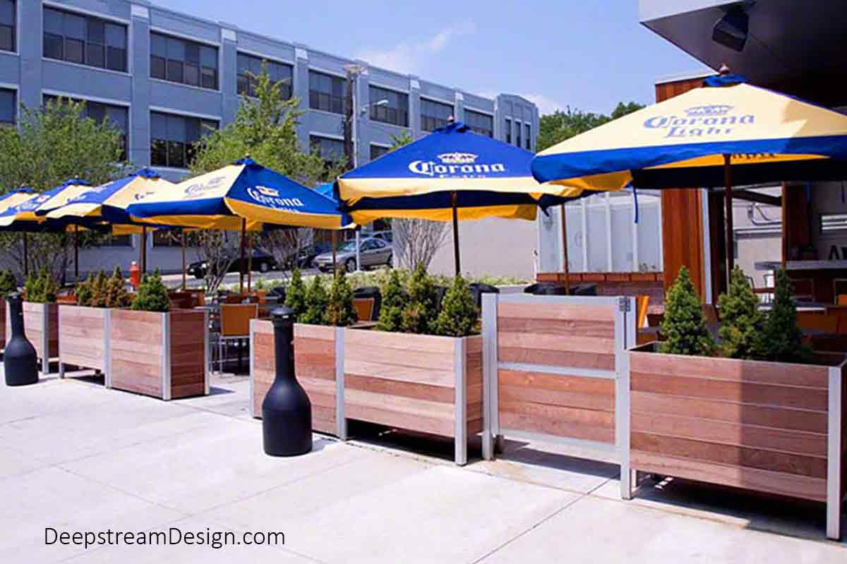 As with this urban street café under blue and gold Corona beer umbrellas next to a University, Planters with Gates that meet Life Safety codes are often required by outdoor restaurants that serve alcohol.