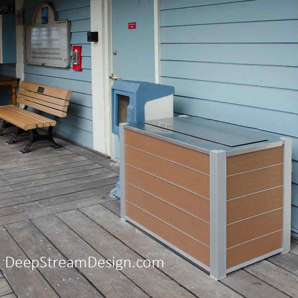 An Audubon double-stream 33-gallon modern commercial combined recycling and trash receptacle crafted with recycled plastic lumber and an optional 316 stainless steel weatherproof, watertight lid shown at a faded blue oceanfront boardwalk casual restaurant.