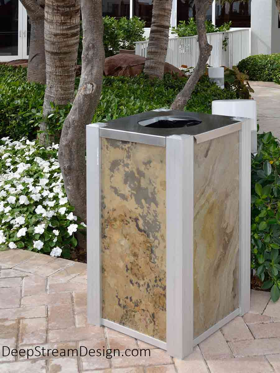 A slim modern commercial outdoor trash bin Audubon 21-gallon receptacle with a top opening stainless lid, aluminum corners, and natural slate panels impervious to tropical weather is situated in a tropical hotel garden with green foliage and masses of small white flowers.
