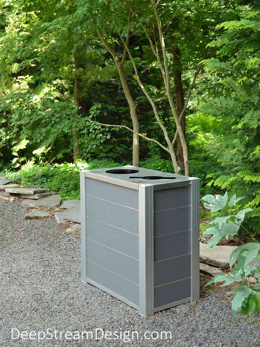 DeepStream Audubon Dual-Stream Commercial Combined Recycling and Trash Receptacle with light gray recycled plastic lumber plank panels on a gravel garden path deep in thick green forest inside Long Island's famous Longhouse Reserve art park.