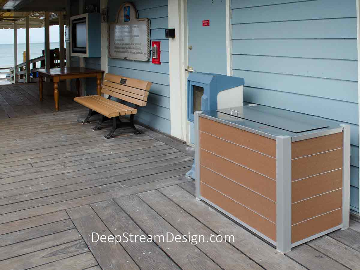 A blue, wooden, casual, tropical beachfront boardwalk restaurant uses DeepStream Audubon Commercial Combined Outdoor dual-stream 33-gallon Recycling and Trash Receptacle constructed with Tropical Hardwood-color recycled plastic lumber plank panels. A 316 stainless steel lid and watertight top keeps out rain, birds, squirrels, possums and racoons.