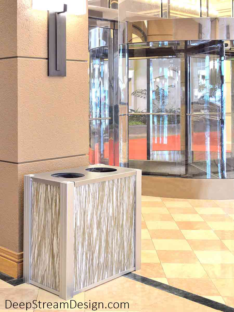A DeepStream Audubon model modern commercial combined recycling and trash receptacle with 316 stainless steel lid, anodized silver aluminum legs, and 3form Eco-Resin panels of natural bear grass provides service in the marble lobby of a 5-star modern luxury hotel.