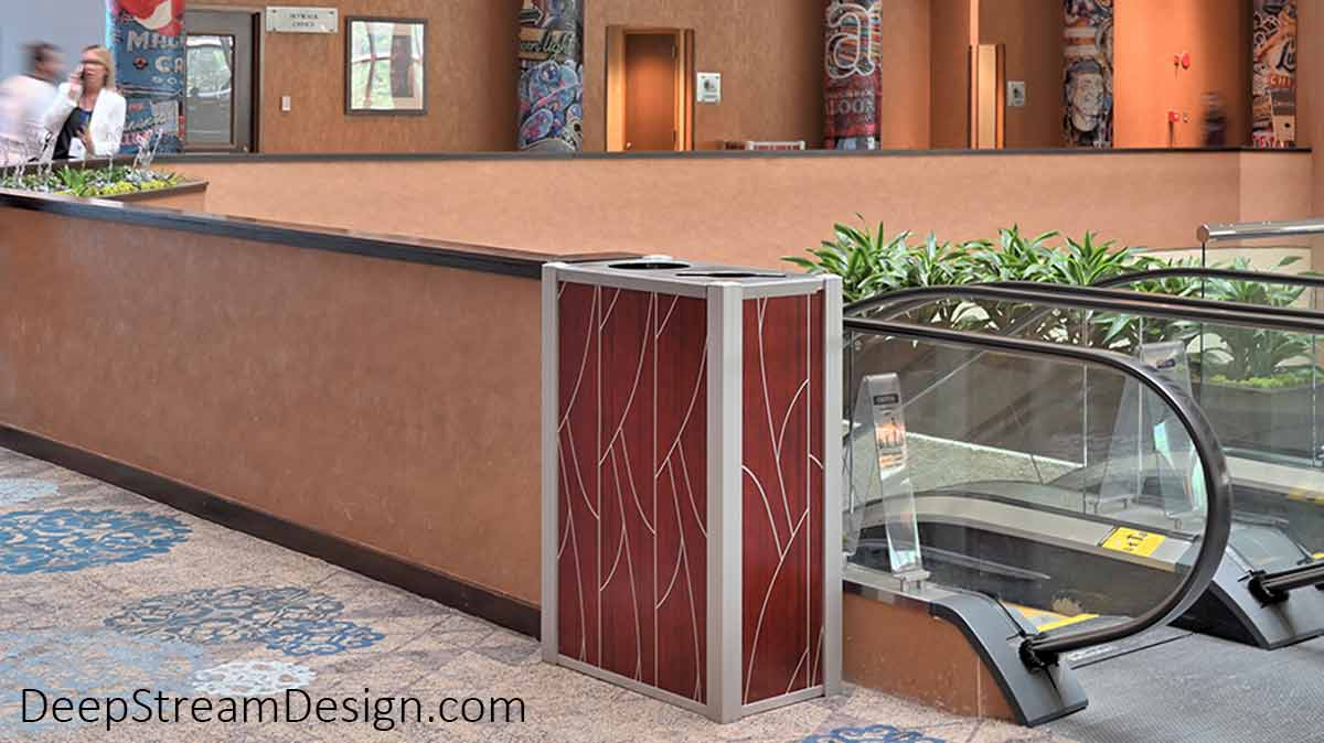 DeepStream Audubon dual-stream 21-gallon modern commercial combined recycling and trash receptacle stands ready to serve on an escalator landing in the atrium of a luxury business hotel. This Audubon bin has a modern silver and dark cherry wood aluminum skin that completes the Hotel Designer's commitment to the final details of the client's vision for this huge, colorful, art-filled space.