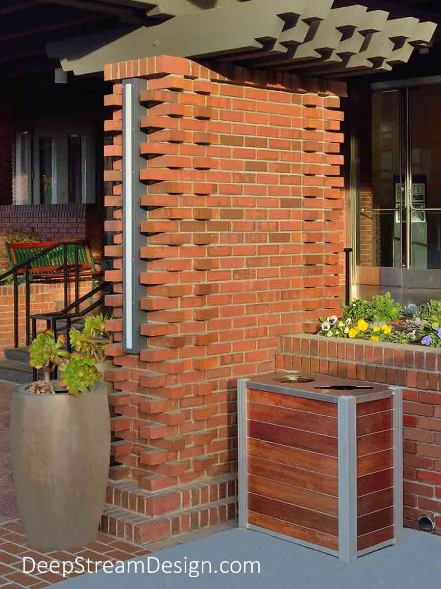 DeepStream Audubon dual-stream Commercial Combined Recycling and Trash Receptacles crafted with wood panels at the steps of a golf resort built in the Pacific Coast Craftsman architectural style with brick and shaped timber and colorful flowers in planters.