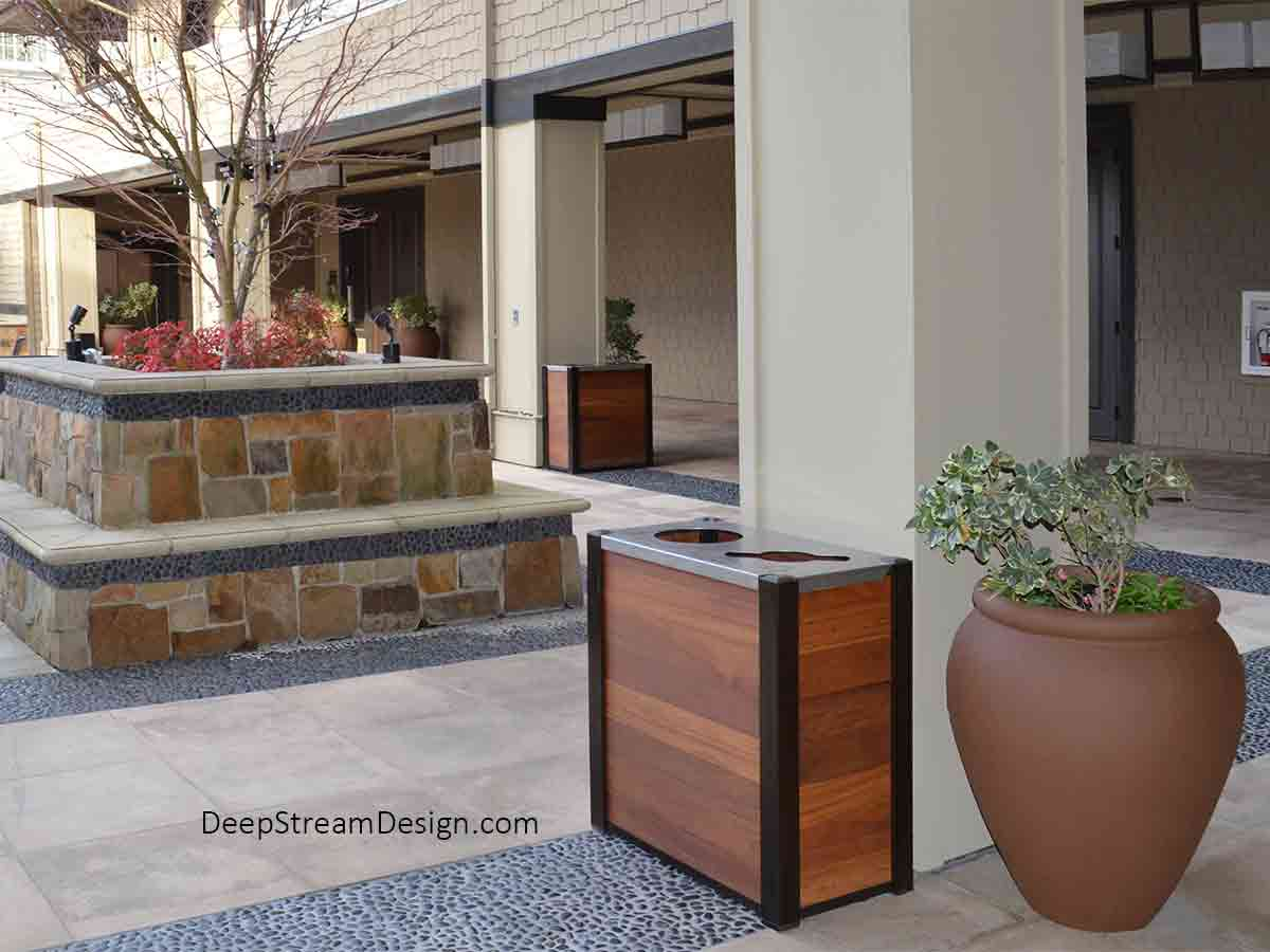 Two 21-gallon dual-stream Audubon modern wood commercial combined recycling and trash receptacles with Cumaru tropical hardwood panels serve outdoors in the courtyard formed of natural flag stone and polished black pebbles at a 5-star wine country hotel just off Napa's Silverado Trail.