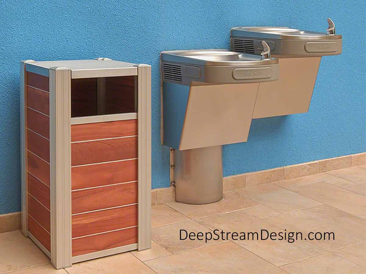 A 17-gallon front-load DeepStream Audubon modern commercial recycling or trash bin, next to a stainless steel drinking fountain attached to a bright blue wall of a tiled courtyard of a commercial building. There is also a 25-gallon capacity interior bin option.