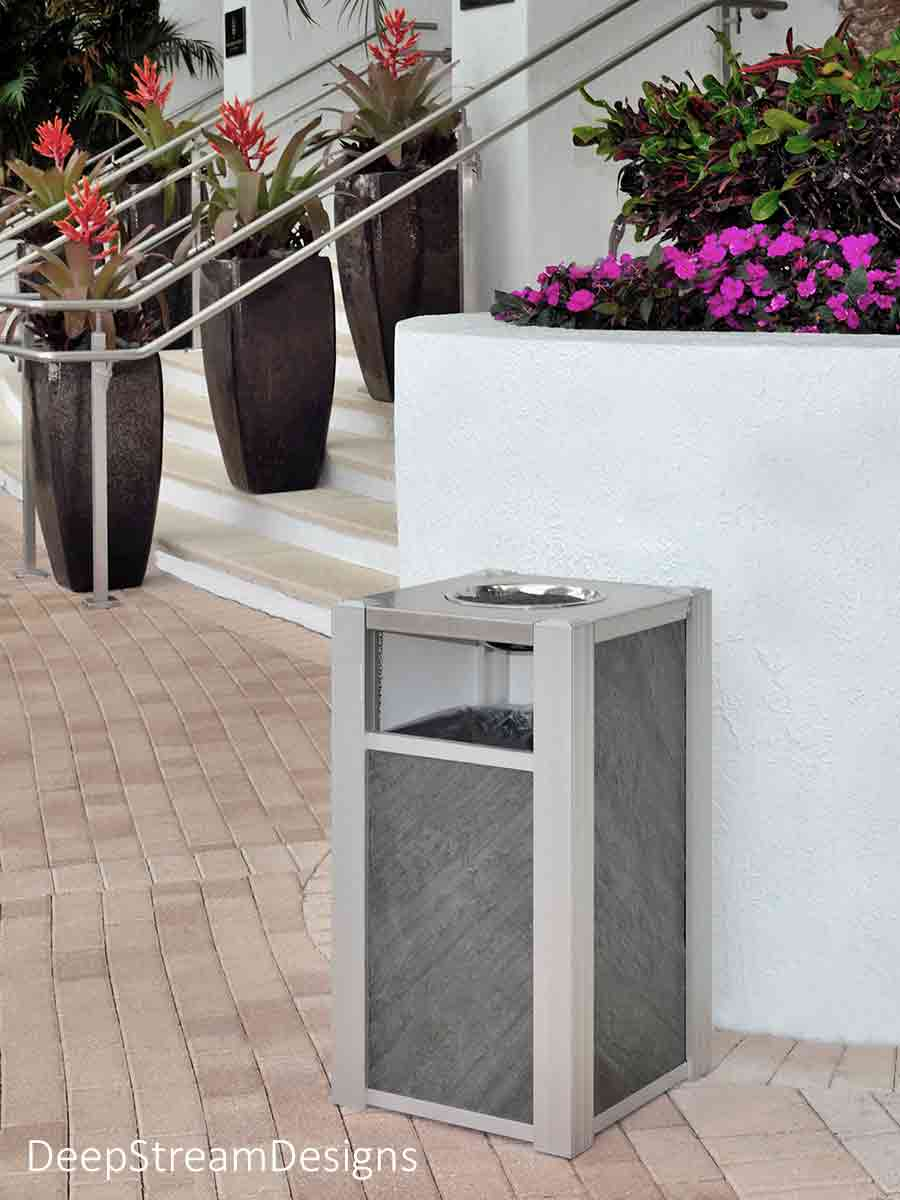 Flanking the steps of a luxury beachfront high-rise resort hotel, DeepStream's Audubon Modern Commercial Trash Cans with ashtray top and natural gray-green slate panels are in keeping with the lushly and brightly landscaped terraced entrance.