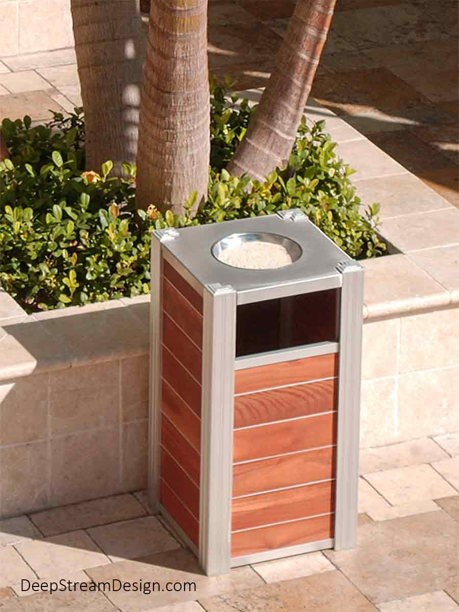 Gracing the tropical courtyard of a rustic marble paved luxury shopping and office complex complete with palm trees, in large stone planters, DeepStream's Audubon Modern Commercial Trash Cans with 316-stainless steel ashtray top and tropical wood panels are in keeping with the luxury vibe