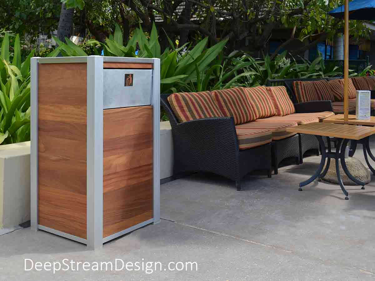 An Oahu Modern Commercial Recycling and Trash Bin with a 316-stainless steel lid, aluminum push flap and anodized aluminum legs, is shown at a lushly landscaped tropical Hawaiian outdoor oceanfront restaurant crafted with the ever-popular classic wood plank panels.