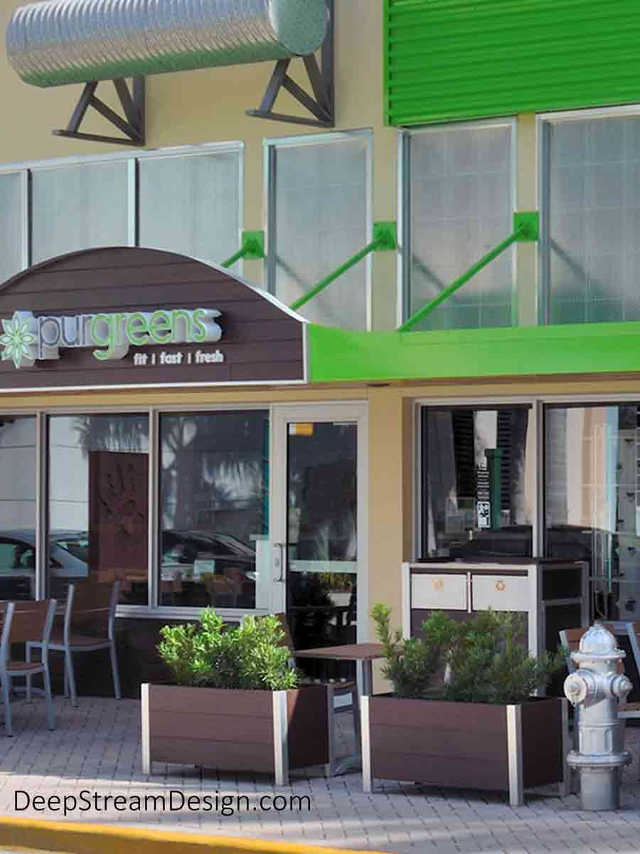A health food restaurant and gym called Purgreens, housed in a bright green and yellow low-rise building, has a dining area under the Florida palms on the fancy brick sidewalk delineated by DeepStream's Ipe Brown recycled plastic lumber restaurant planters with a companion twin-stream Commercial Combined Recycling and Trash Receptacle.