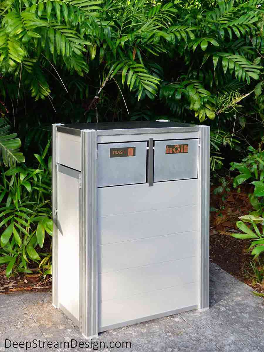 Sitting on a path through a humid, overgrown, dark green jungle garden, the Oahu Commercial Combined Recycling and Trash Receptacle is in its element. Crafted with Light Gray-colored no-maintenance recycled plastic lumber held by marine-anodized proprietary aluminum extrusions and fitted with 316 stainless steel lid and hinges, marine aluminum push flaps, and ergonomic door to remove the leakproof 21-gallon inner bins, the Oahu is oblivious to the wet conditions.