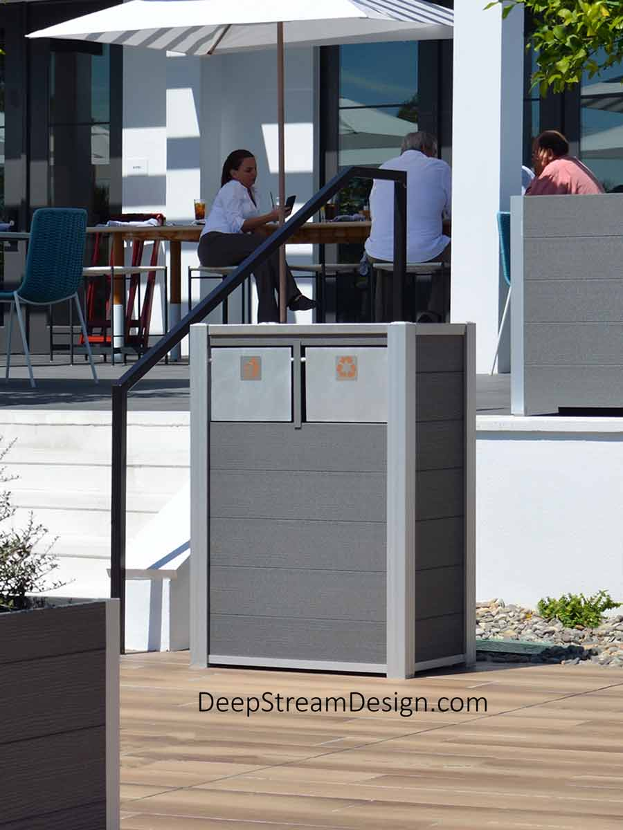Often seen as it is here at the entrance to a modern outdoor seating section of a restaurant with tables set under large shade umbrellas, this Oahu dual-stream Commercial Combined Recycling and Trash Receptacle is crafted with modern Light Gray-colored no-maintenance recycled plastic lumber. Standard construction includes 316 stainless steel lid and hinges, marine aluminum push flaps, and ergonomic door to remove the leakproof 33- or 21-gallon inner bins.