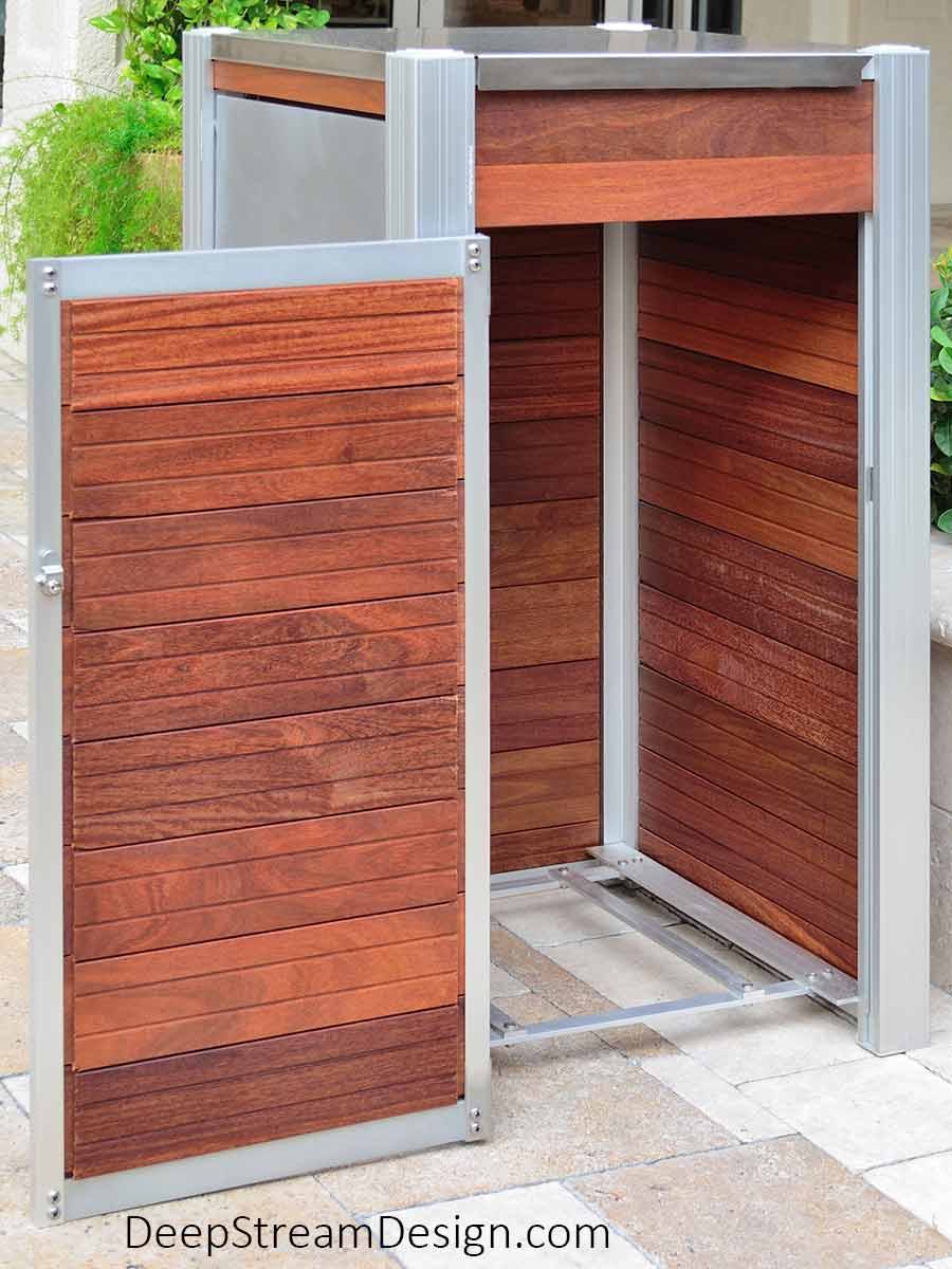 A 33-Gallon Oahu Modern Commercial Recycling and Trash Bin constructed with wood panels on natural stone in an exterior courtyard of an up-scale tropical shopping mall and commercial office building. The interior bin access door is open showing design and construction details, including the open sanitary aluminum grid designed to support the leakproof inner plastic bin so that there is no place for dirt or pests to hide.