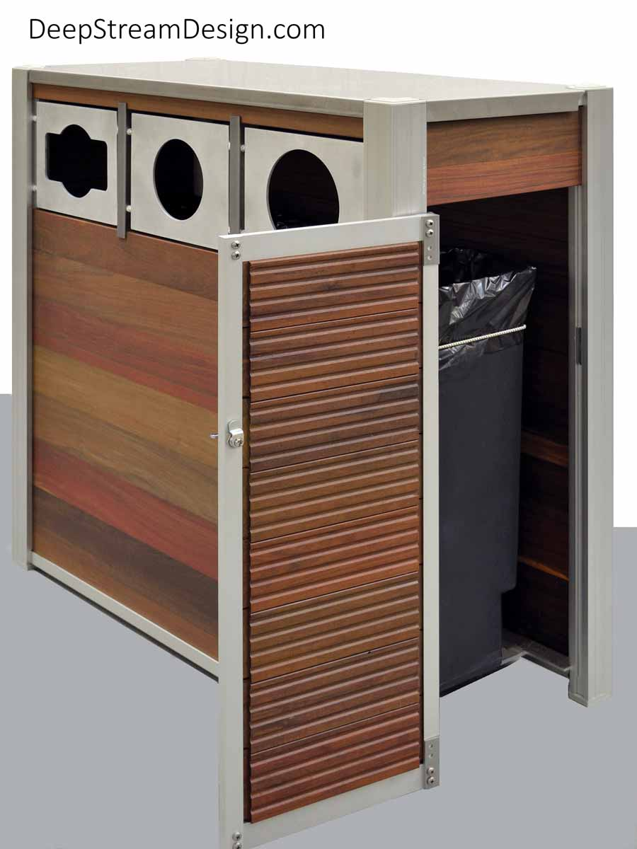 Detailed studio photo showing an Oahu triple-stream Modern Commercial Combined Recycling and Trash Receptacle constructed with Ipe tropical hardwood for outdoor use, fixed marine aluminum front openings for trash and commingled recycling, and a 16-gauge 316 stainless steel lid. The ergonomic door is open showing the leakproof 21-gallon inner bins resting on a sanitary open aluminum grid that gives no place for pests or dirt to hide.
