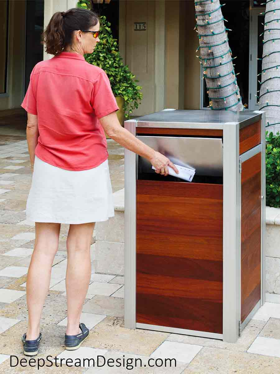 Oahu Commercial Wood Recycling and Trash Bin with aluminum legs, 316 stainless steel hinged lid, ergonomic side door, leakproof 33-gallon inner bin, and Jatoba wood side panels shown in the courtyard of a high-end, tropical, Mediterranean style shopping plaza with stone pavers and palm trees with a woman placing rubbish into the bin through a large aluminum push flap.