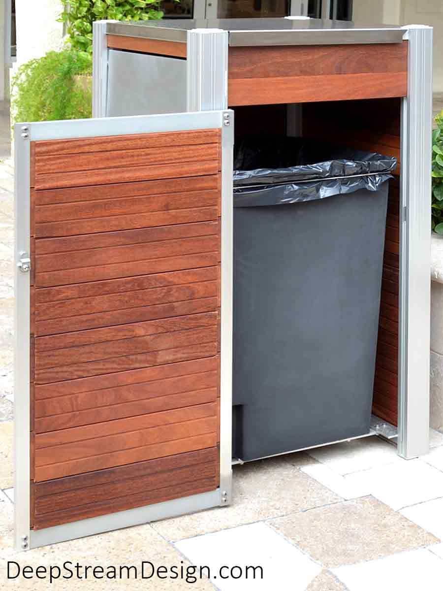 Oahu Commercial Wood Recycling and Trash Bin with aluminum legs, 316 stainless steel hinged lid, ergonomic side door, leakproof 33-gallon inner bin, and Jatoba wood side panels shown in the courtyard of a high-end, tropical, Mediterranean style shopping plaza with stone pavers and palm trees. The side door access to the inner bin is open to show the open grid that supports the inner bins.