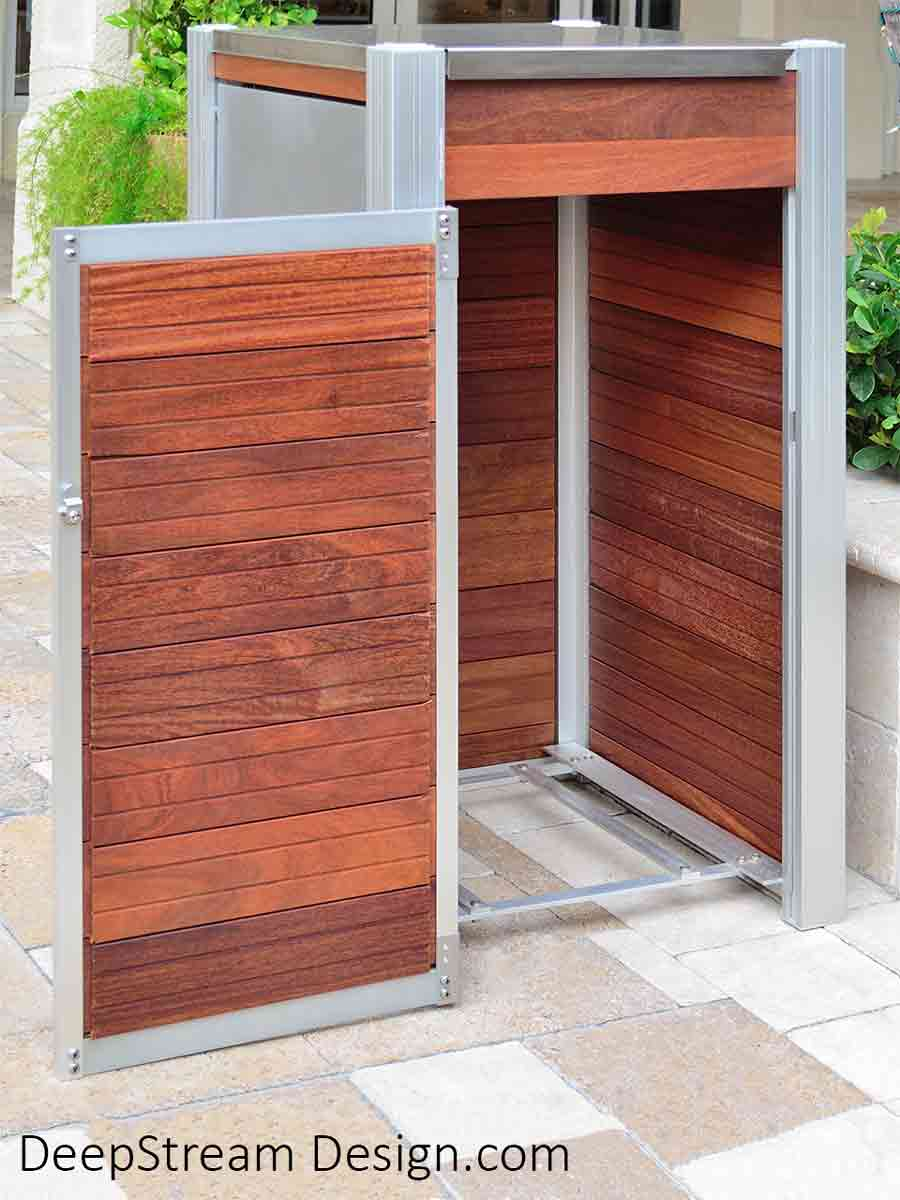 Oahu Commercial Wood Recycling and Trash Bin with aluminum legs, 316 stainless steel hinged lid, ergonomic side door, leakproof 33-gallon inner bin, and Jatoba wood side panels shown in the courtyard of a high-end, tropical, Mediterranean style shopping plaza with stone pavers and palm trees. The side door access to the inner bin is open and the bin removed to show the open grid that supports the inner bins.