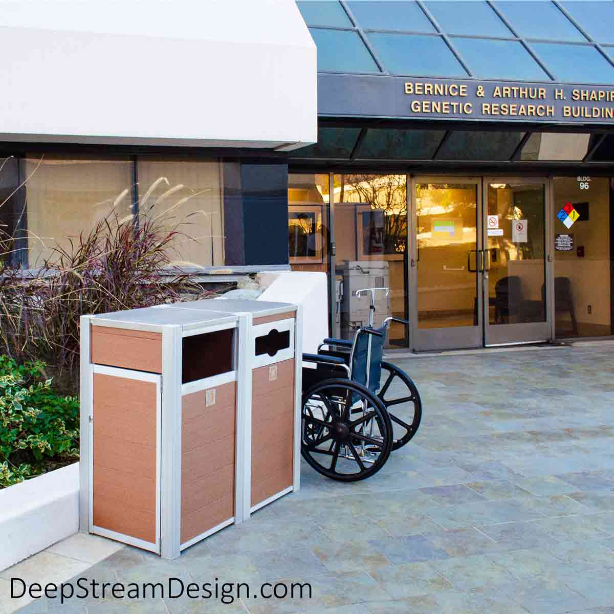 On the hospital grounds of a world-class research hospital, a high-volume 33-gallon Oahu Modern Commercial Recycling Receptacle, with a no-touch fixed comingled front flap, serves alongside a no-touch open front Modern Commercial Trash Bin. Both are crafted with DeepStream's trademark marine-anodized aluminum legs. Tropical Hardwood recycled plastic lumber plank panels, 316 stainless steel lids and hinges, ergonomic side doors for bag changes, and marine aluminum fixed flap.