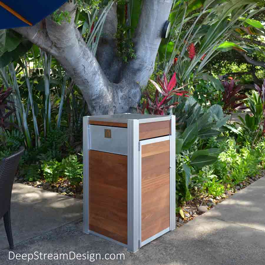Oahu Modern Commercial Wood Recycling and Trash Bin with a side door and aluminum push flap and 316 stainless steel top at an outdoor tropical island beachside restaurant set under blue umbrellas at the edge of a verdant jungle with trees, dark green plants and bright red leaves.