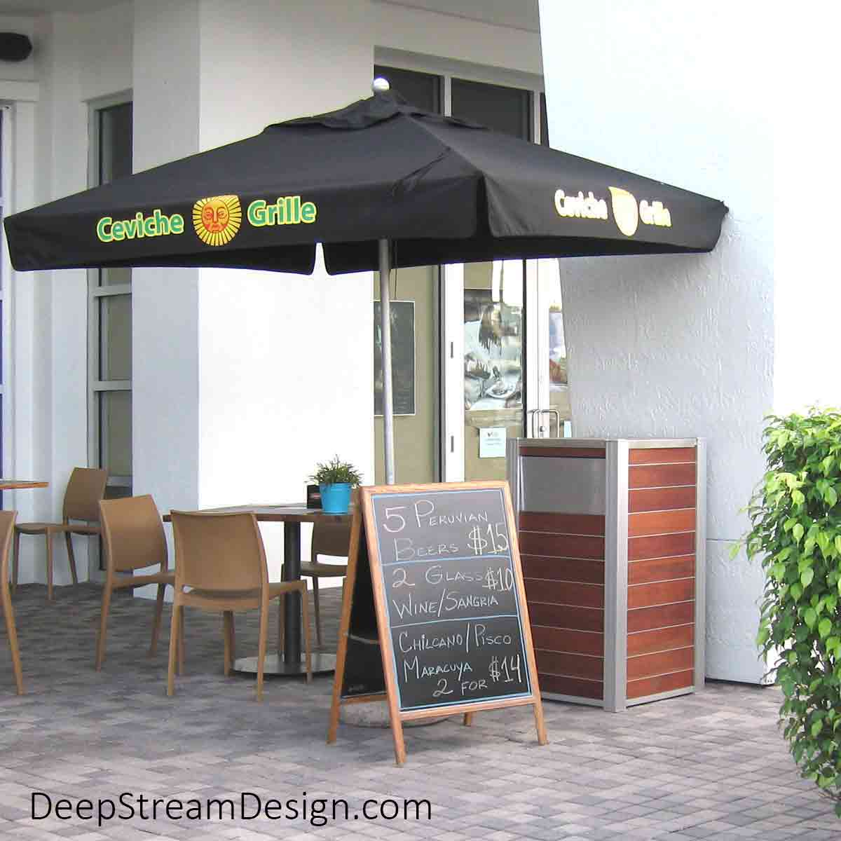 An Oahu Modern Commercial Wood Recycling and Trash Bin crafted with Cumaru tropical hardwood, 316 stainless steel lid for bag changes, an aluminum push flap matching the silver anodized aluminum leg, fit the modern décor of an upscale shopping center sidewalk Ceviche Restaurant with aluminum and leather chairs and tables under black umbrellas.