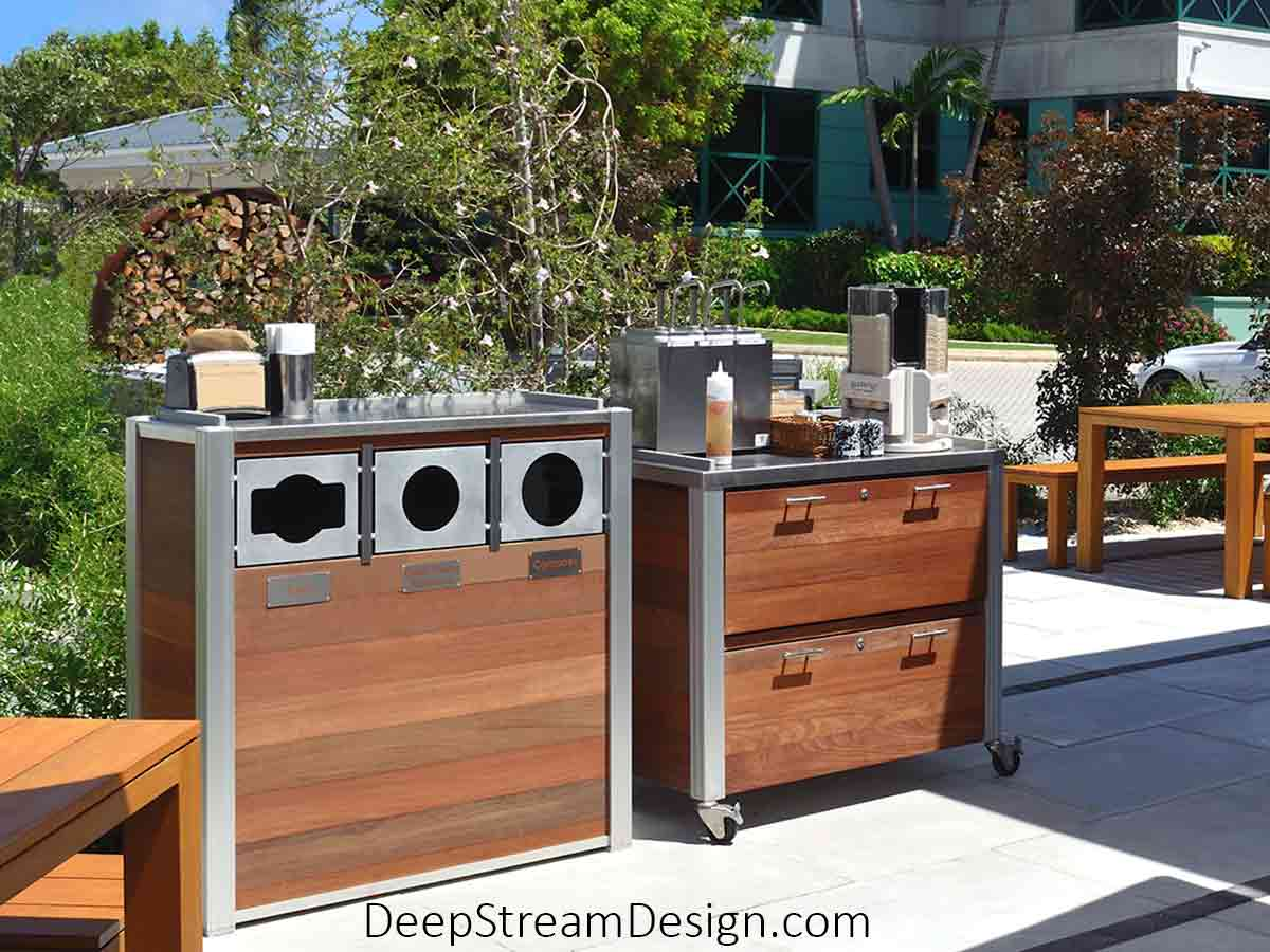 Pictured at a tropical island's upscale outdoor restaurant, an Oahu triple-stream Modern Commercial Combined Recycling and Trash Receptacle constructed with Ipe tropical hardwood for outdoor use, fixed marine aluminum front openings for trash and comingled recycling, and a 16-gauge 316 stainless steel lid. The leakproof 21-gallon inner bins rest on a sanitary open aluminum grid that gives no place for pests or dirt to hide. A companion food service cart restaurant fixture is constructed with wood drawer fronts and food service-grade waterproof HDPE inner drawers opening on 316 stainless steel roller slide supports and caster wheels for mobility.