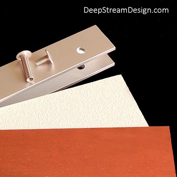 A studio photo showing how DeepStream's proprietary aluminum channel extrusion captures the thinnest version an expensive piece of real copper, or any other material, with an inexpensive backer panel to form a cost-effective panel for Custom Commercial Combined Recycling and Trash Receptacles and Commercial Recycling and Trash Bins.