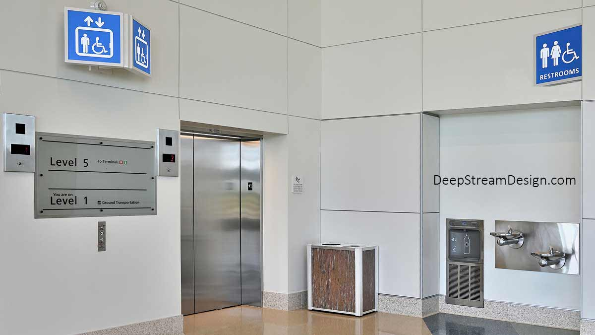 DeepStream Audubon dual-stream modern commercial combined recycling and trash receptacle with 3form Eco-Resin panels in the elevator lobby of a modern intermodal transit center with a water bottle filling station, drinking fountains, and restrooms.