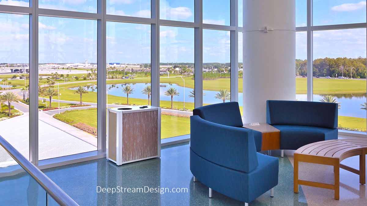 America's newest International Airport is exceptional in every respect and filled with DeepStream Audubon dual-stream modern commercial combined recycling and trash receptacles with 3form Eco-Resin panels like this one in a waiting area with blue couches and wood coffee tables overlooking a calm palm tree-lined lake.