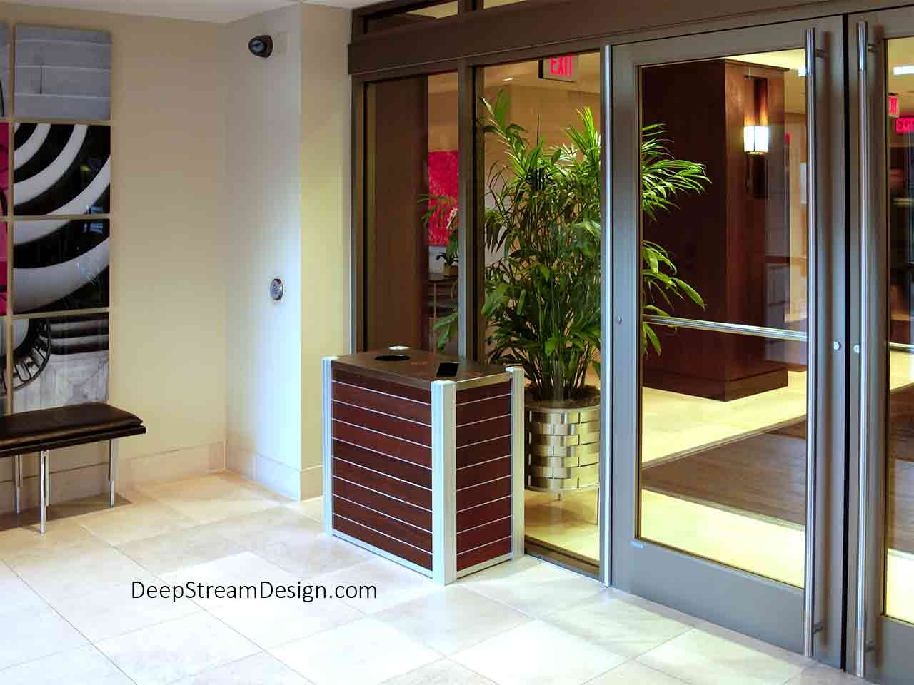 A small boutique hotel lobby filled with art looks more like the entrance to swanky private club, a perfect place for a DeepStream Audubon dual-stream modern commercial combined recycling and trash receptacle with dark Ipe Wood panels separated by Zephyr aluminum bands.