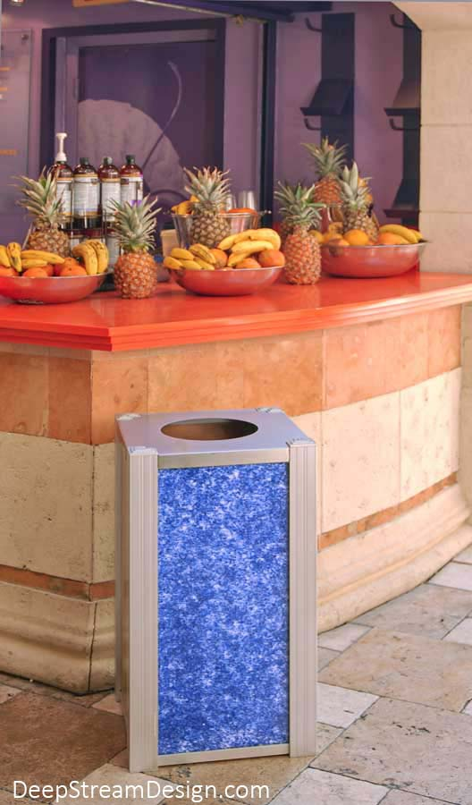 DeepStream's Audubon modern custom outdoor restaurant trash can, crafted with bright blue recycled crushed glass 3form-Eco Resin panels, accent a popular fresh fruit drink stand alive with personality and bright tropical fruit colors at a Mediterranean style outdoor shopping area.