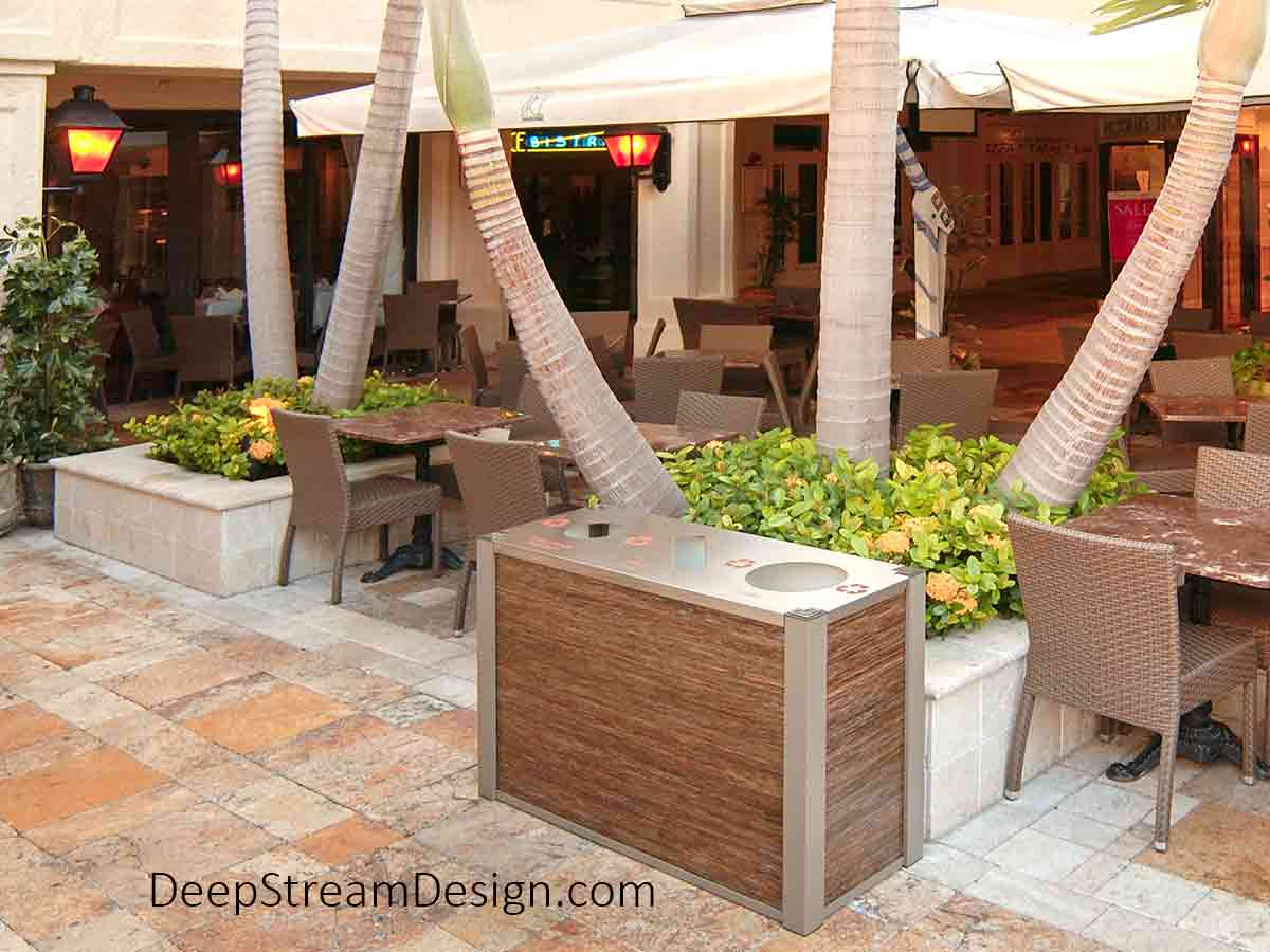 An elegant plaza restaurant with woven wicker-look chairs and marble tables under tan umbrellas uses DeepStream Audubon Commercial Combined Outdoor triple-stream 21-gallon Recycling and Trash Receptacles constructed with 3form Eco-resin panels.