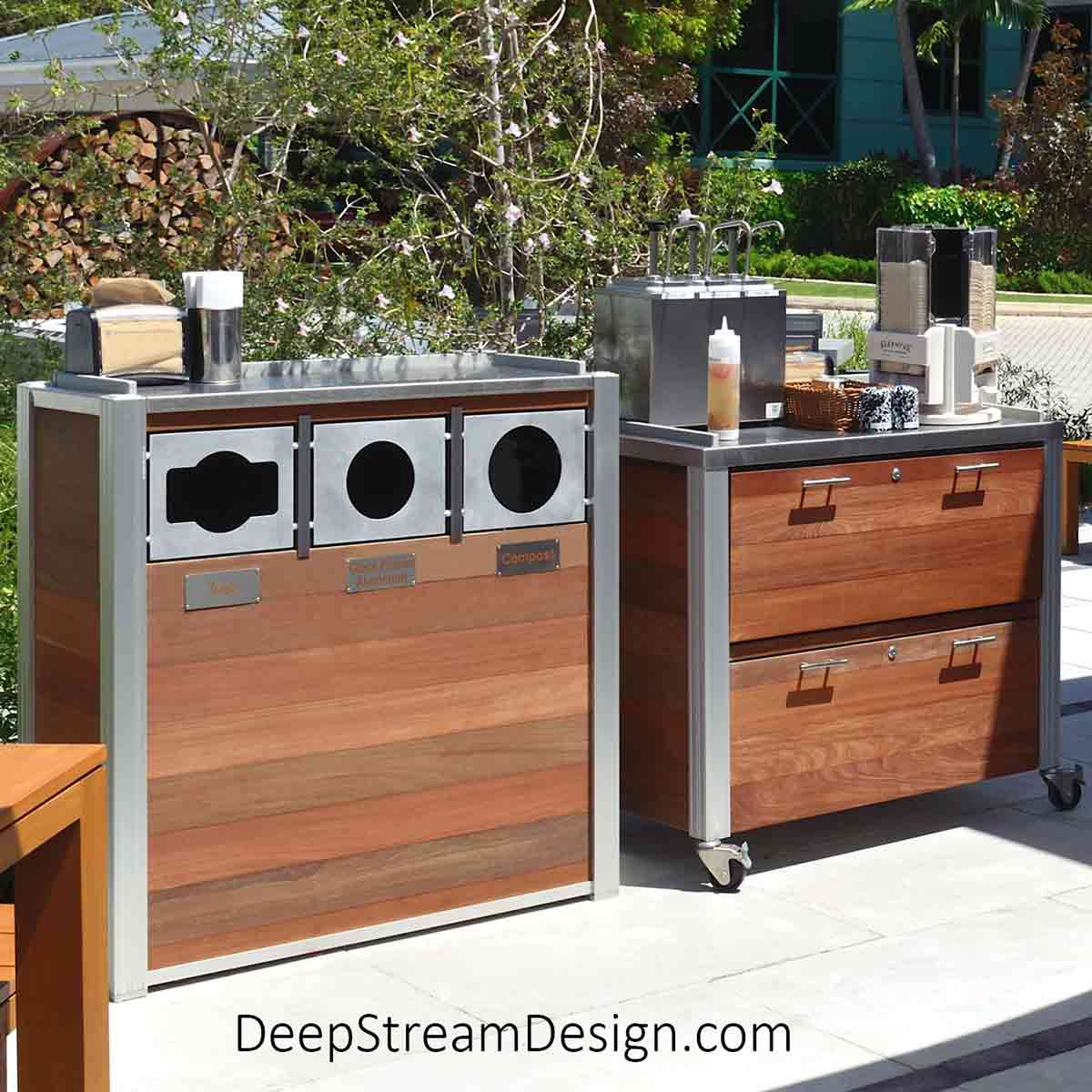 A modern custom outdoor restaurant trash receptacle on wheels next to a companion food service cart at a tropical island cafe. Both are made with a 316 stainless steel top, anodized aluminum frame, and exterior grade Ipe Tropical Hardwood.