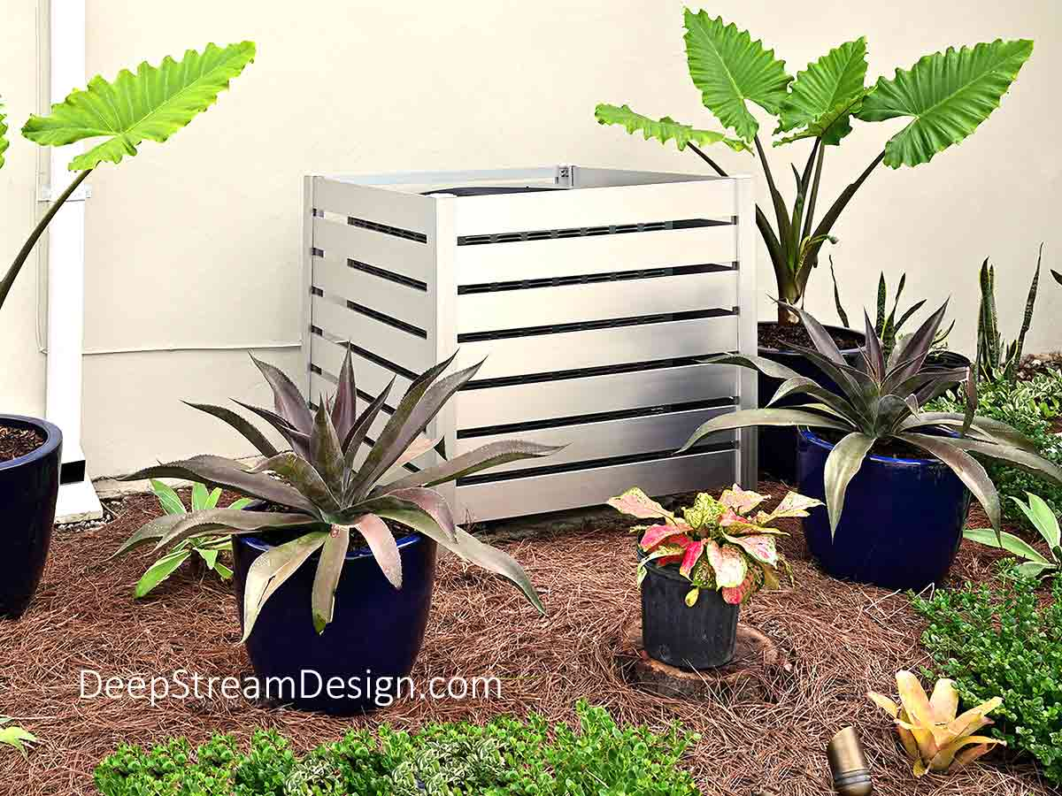 A ground level residential Air-conditioner situated in a garden against the house wall but in plain sight of a pool and sundeck is covered by a silver aluminum Air-Conditioning Equipment Screen. The Equipment Screen is fabricated as a free standing 4-sided box with 4-inch aluminum planks that are spaced an inch apart and has an open top for enhanced air circulation. The 7 aluminum planks that make up each side panel are one unit so they may be quickly lifted out giving full access to the AC unit for service while allowing for the smallest screen wall enclosure footprint.