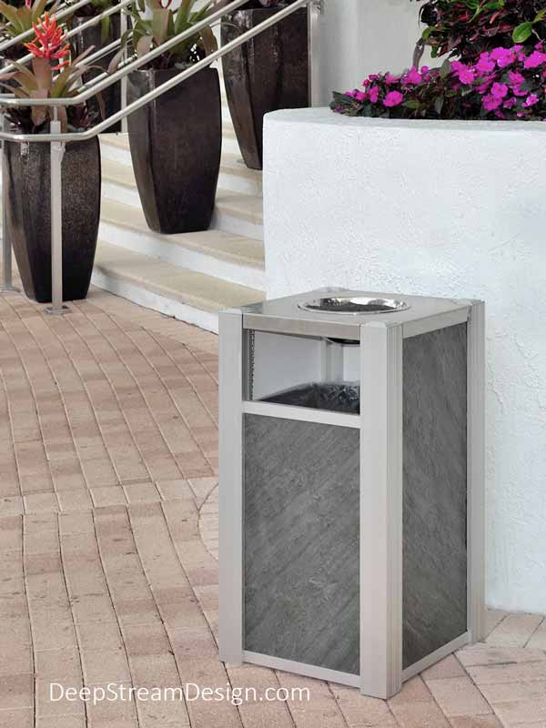 An Audubon Modern Commercial Ash Trash Bin with ashtray top, with Ocean Black side panels using TXTR-LITE flexible natural stone veneer, serves guests entering a 5-star resort hotel.