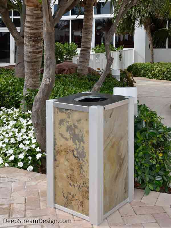 An Audubon Modern Commercial Recycling Receptacle or Trash Bin, with side panels using TXTR-LITE Indian Autumn flexible natural stone veneer, serves hotel guest in the tropical garden and pool areas of an oceanfront luxury hotel.