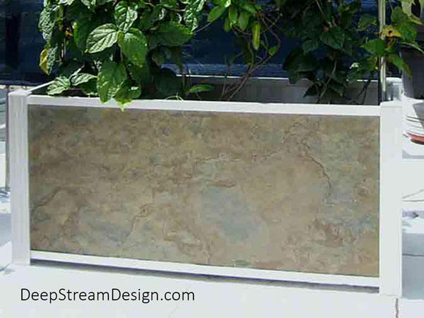 A modern Audubon garden planter, with TXTR-LITE Golden Slate natural stone veneer panels, adds variety to the planters on a tropical penthouse roof deck.