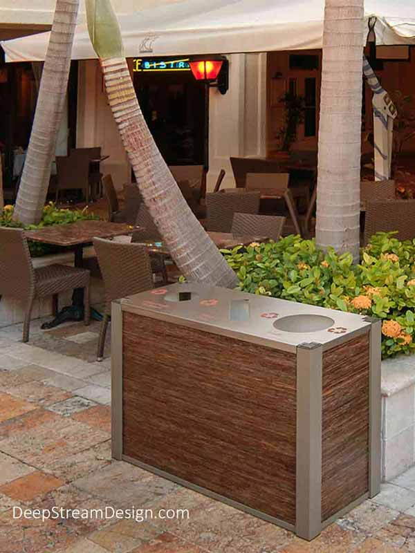 Audubon triple-stream Modern Commercial Combined Recycling and Trash Receptacle with 3-form Natural Banana Fiber Varia Ecoresin panels complement the wicker seating while serving duty in the stone paved outdoor courtyard of an upscale Italian restaurant under large umbrellas.
